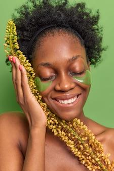 肌の色が濃い女性が目を閉じて笑顔を保ち、天然ハーブ製品を幅広く使用し、巻き毛があります。
