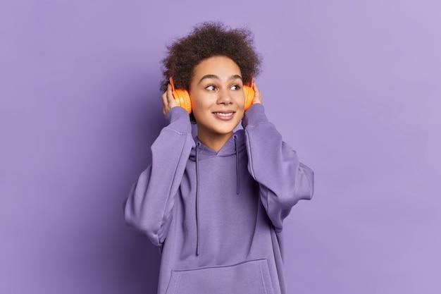 곱슬 덥수룩 한 머리카락을 가진 만족스러운 어두운 피부의 여성은 스테레오 헤드폰을 착용하고 운동복을 입은 음악을 듣습니다.