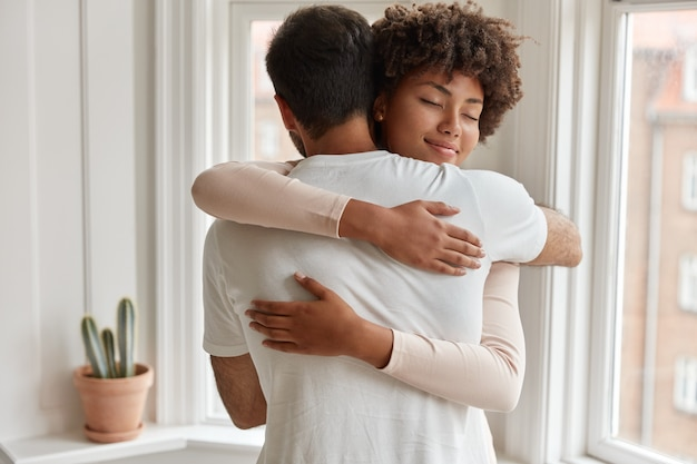 Pleased dark skinned young woman gives warm hug to her boyfriend, being pleased, pose near window, have romantic relationship, stand in cozy room. husband and wife feel pleased and togetherness