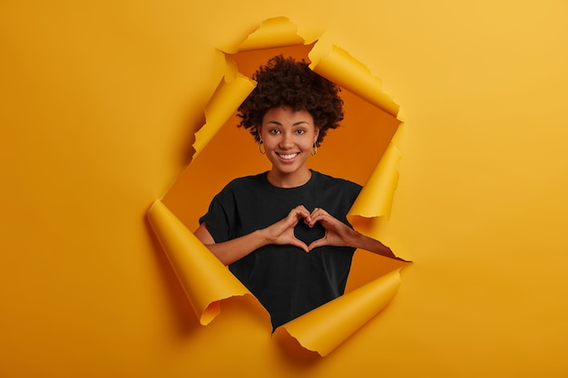 Pleased dark skinned young woman shows heart symbol, shapes love sign with hands, smiles happily, wears black t shirt and earrings