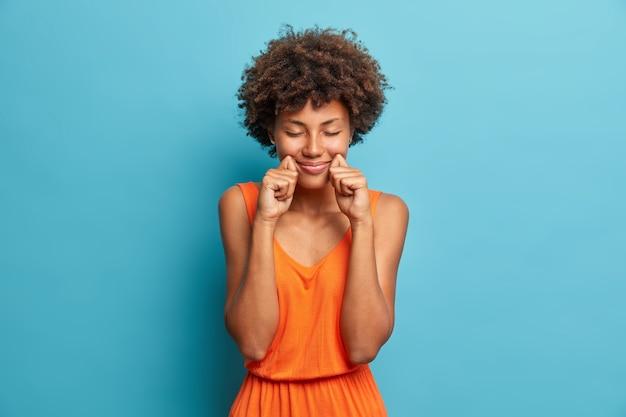 目を閉じて立っている満足している暗い肌の若い女性は、頬と笑顔の近くに手を保ちます
