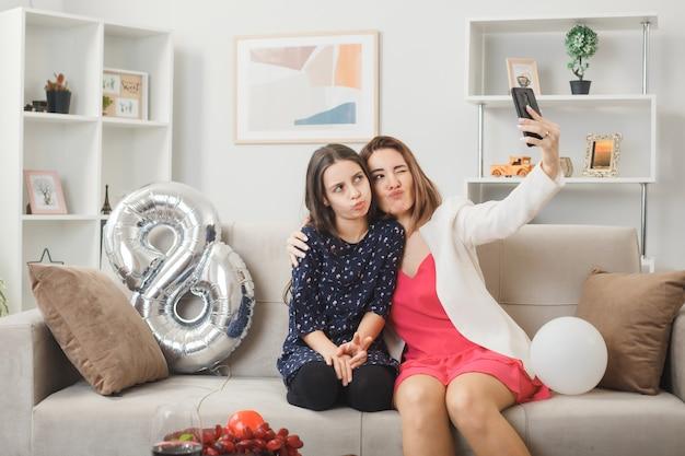 ソファに座って幸せな女性の日に満足している娘と母は、リビングルームで自分撮りをします
