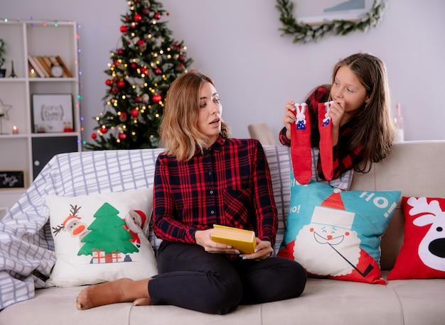 Довольная дочь держит чулки, стоя позади своей матери, читает книгу, сидя на диване и наслаждается рождеством дома