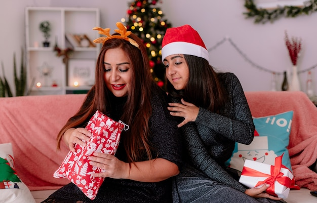 Figlia e madre felici guardano il regalo della madre seduta sul divano schiena contro schiena godendo il periodo natalizio a casa