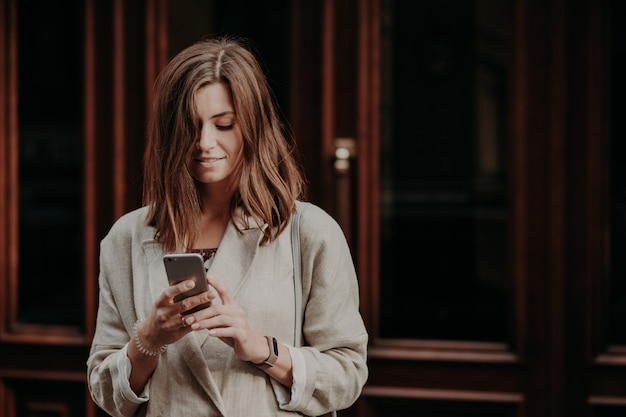 Pleased delighted female youngster watches video on smart phone