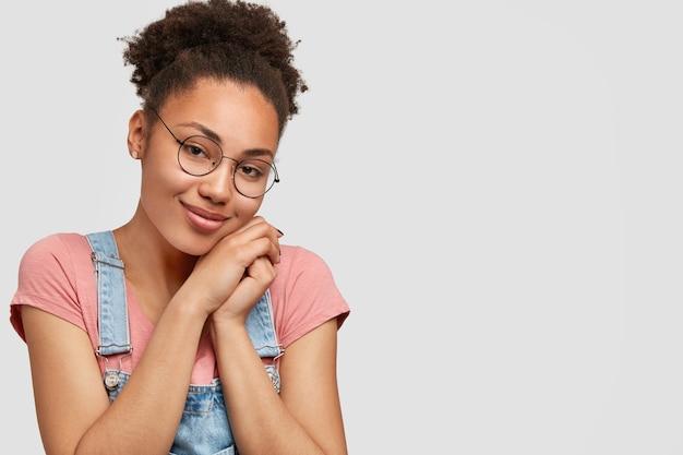 黒い肌、魅力的な外観、あごの下で手をつなぎ合わせ、眼鏡とカジュアルな服を着て、自由なスペースのある白い壁の上でポーズをとる、喜んで喜んでいる若いアフリカ系アメリカ人女性