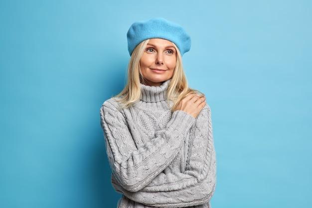 기뻐하는 꿈꾸는 금발의 유럽 여성은 상냥한 만족스러운 표정으로 베레모와 니트 점퍼를 착용하고 잠겨있는 표정으로 거리에 집중했습니다.