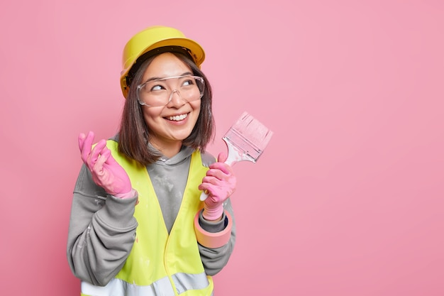 Pleased dreamy cheerful female maintenance worker holds paint brush wears special clothes ready for doing reconstruction concentrated away