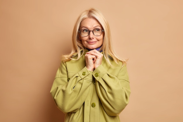 Pleased dreamy senior woman keeps hands pressed together under chin ponders idea wears optical glasses green jacket.