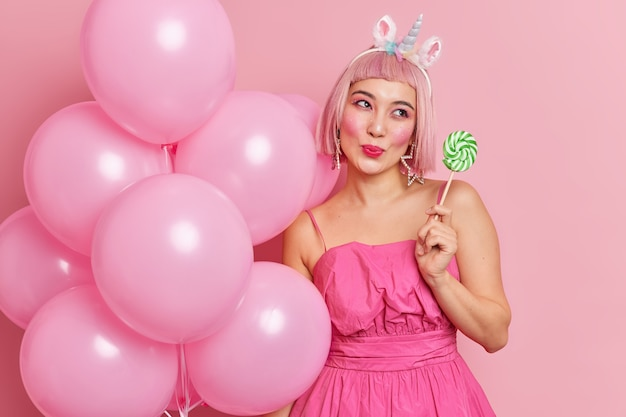 Pleased dreamy woman with pink hair holds green round candy on stick likes sweet lollipops