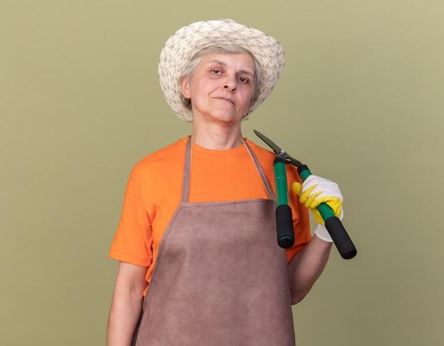 복사 공간이 있는 올리브 녹색 벽에 격리된 어깨에 정원 가위를 들고 정원 가꾸기 모자와 장갑을 끼고 기뻐하는 노인 여성 정원사