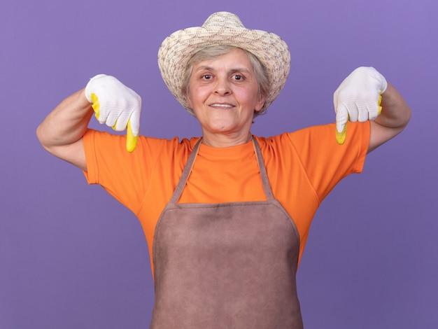 원예용 모자와 장갑을 낀 행복한 노년 여성 정원사는 복사 공간이 있는 보라색 벽에 고립되어 있습니다