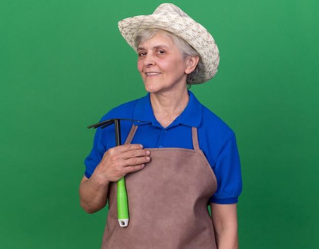 복사 공간이 있는 녹색 벽에 격리된 괭이 갈퀴를 들고 원예용 모자를 쓴 노인 여성 정원사를 기쁘게 생각합니다.
