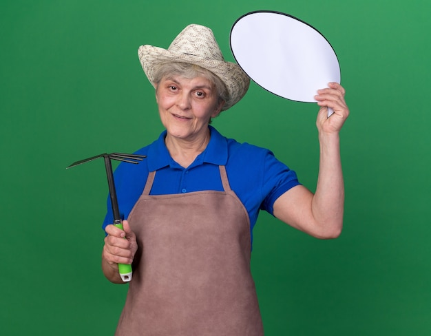 Felice donna anziana giardiniera che indossa cappello da giardinaggio tenendo rastrello zappa e fumetto