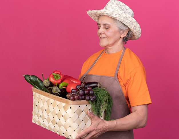 Lieta giardiniera anziana che indossa cappello da giardinaggio che tiene e guarda un cesto di verdure