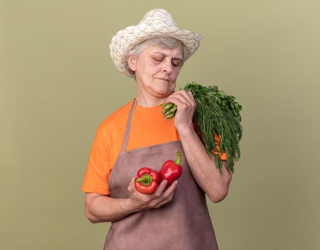 Lieta anziana giardiniere femmina indossando giardinaggio hat holding peperoni rossi mazzetto di coriandolo e aneto isolato su verde oliva parete con spazio di copia