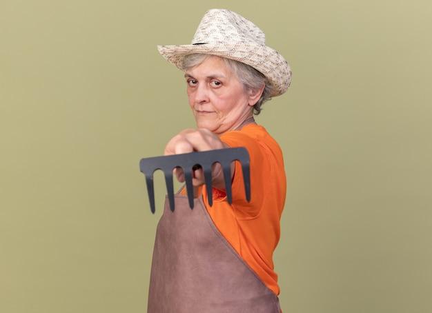 Il giardiniere femmina anziana felice che indossa il cappello da giardinaggio si erge lateralmente tenendo fuori il rastrello