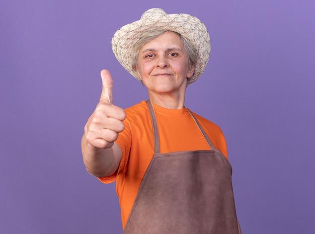 Piacere anziana giardiniera femmina che indossa cappello da giardinaggio pollice in alto isolato sulla parete viola con spazio copia