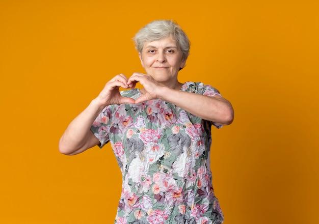 Felice donna anziana gesti cuore mano segno isolato sulla parete arancione