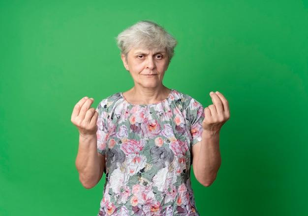 Довольная пожилая женщина жестикулирует знак рукой деньги, глядя изолированным на зеленой стене