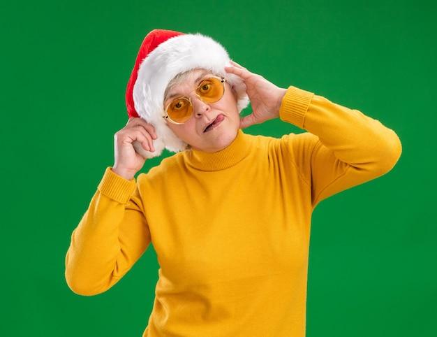 Довольная пожилая женщина в солнцезащитных очках в шляпе санта-клауса высунула язык на зеленой стене с копией пространства