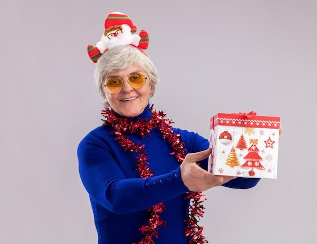 산타 머리띠와 목 주위에 갈 랜드와 태양 안경에 기쁘게 노인 여성 복사 공간이 흰 벽에 고립 된 크리스마스 선물 상자를 보유