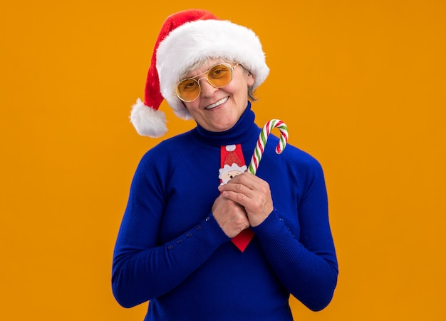 Pleased elderly woman in sun glasses with santa hat and santa tie holding candy cane isolated on orange wall with copy space