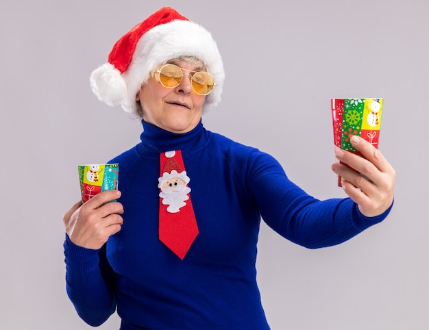 Pleased elderly woman in sun glasses with santa hat and santa tie holding and looking at paper cups isolated on white wall with copy space