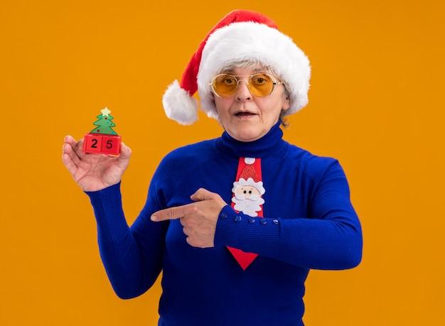Felice donna anziana in occhiali da sole con cappello da babbo natale e cravatta da babbo natale che tiene e punta all'ornamento dell'albero di natale isolato sulla parete arancione con spazio di copia