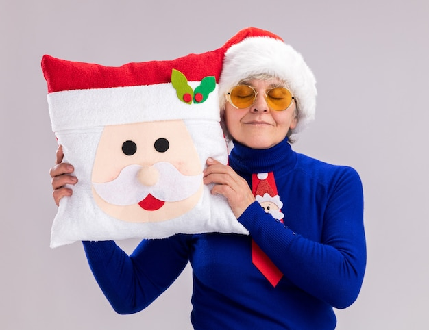 Pleased elderly woman in sun glasses with santa hat and santa tie holding santa pillow isolated on white wall with copy space