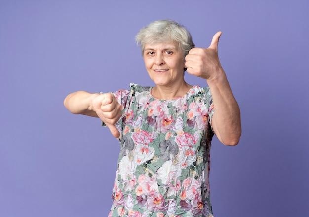 Довольная пожилая женщина показывает палец вверх и палец вниз, изолированную на фиолетовой стене