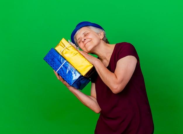 Donna anziana soddisfatta che indossa il cappello del partito che tiene i contenitori di regalo sul verde