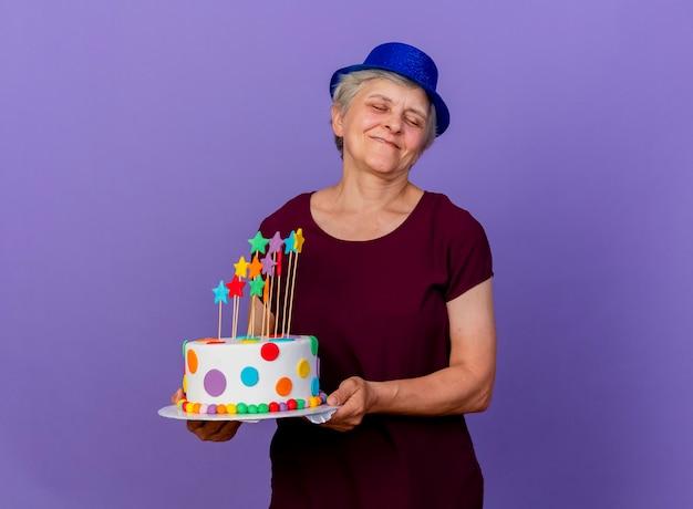 Felice donna anziana indossando il cappello del partito tiene la torta di compleanno isolata sulla parete viola