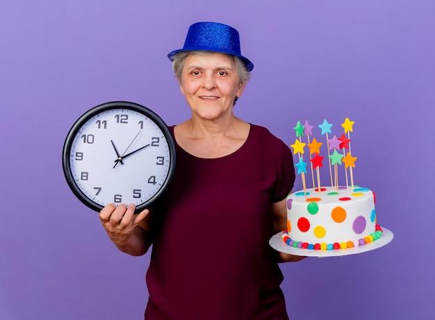 Il cappello da portare della festa della donna anziana soddisfatta tiene l'orologio e la torta di compleanno isolata sulla parete viola con lo spazio della copia