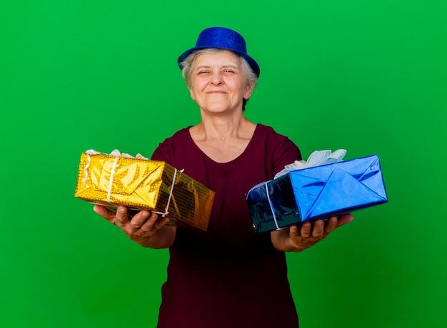 La donna anziana soddisfatta che porta il cappello del partito tiene i contenitori di regalo sul verde