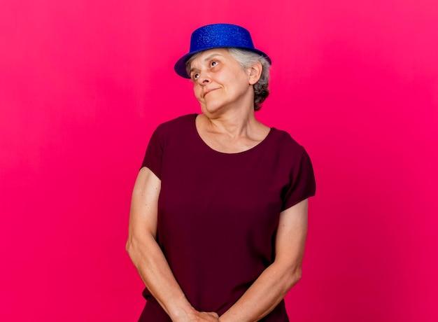 ピンクの側を見てパーティハットをかぶって喜んでいる年配の女性