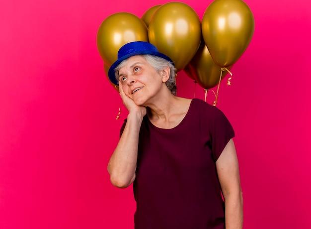 Felice donna anziana che indossa il cappello da festa si trova di fronte a palloncini di elio mettendo la mano sul viso sul rosa