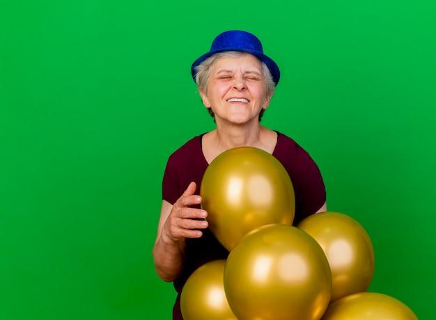 パーティーハットを身に着けている幸せな年配の女性は、コピースペースと緑の壁に隔離されたヘリウム気球で立っています