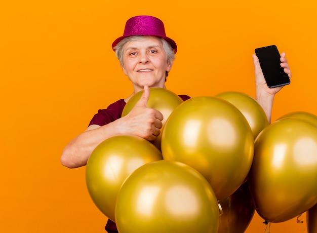 Felice donna anziana che indossa il cappello da festa sta con i pollici di palloncini di elio e tiene il telefono isolato sulla parete arancione