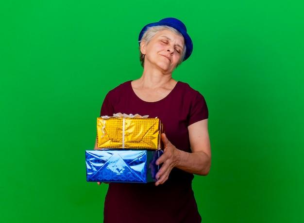 La donna anziana soddisfatta che porta il cappello del partito con gli occhi chiusi tiene le scatole regalo sul verde