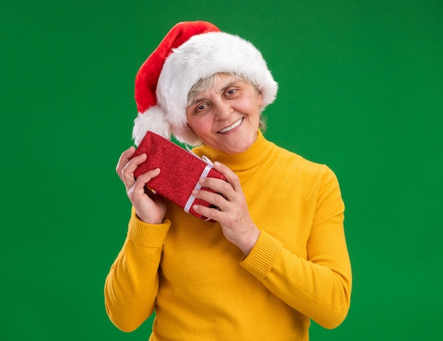Pleased elderly woman with santa hat holds christmas gift box