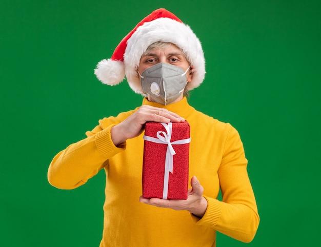 コピースペースで緑の背景に分離されたクリスマスギフトボックスを保持している医療マスクを身に着けているサンタ帽子を持つ年配の女性を喜ばせる