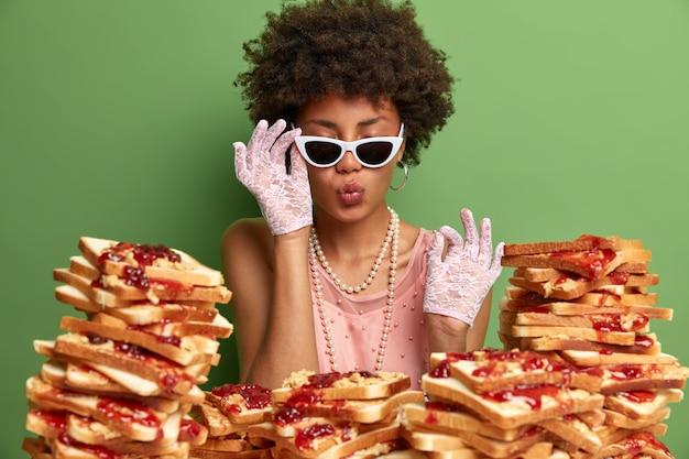 La signora elegante e soddisfatta indossa guanti, vestito e collana di pizzo, sta con gli occhi chiusi, tiene le labbra arrotondate e gli occhiali da sole, non vede l'ora di mangiare deliziosi snack alla marmellata, isolato sul verde