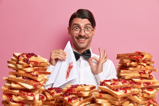 Pleased elegant man cafe visitor adjustes bowtie, being hungry and ready for eating delicious toasts with jam, holds napkin, has polite manners, isolated on pink wall. people, eating concept
