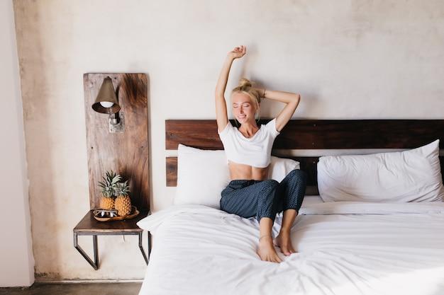 ベッドに座って喜んでエレガントな女性。彼女の居心地の良いフラットで週末を過ごす白人女性。