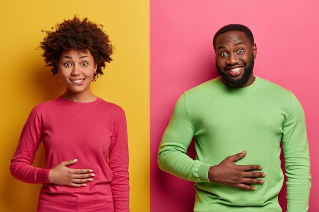 Довольные этнические молодая женщина и мужчина держат руки на животе, чувствуют сытость после вкусного питательного обеда, позитивно улыбаются, счастливы не быть голодными, позируют на фоне желто-розовой стены