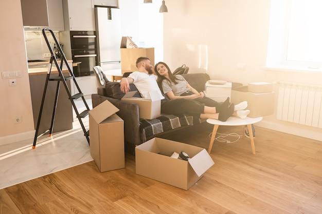 Довольная европейская пара сидит и отдыхает на диване у себя дома. концепция переезда в новую квартиру. идея молодой семьи. картонные коробки с вещами. интерьер однокомнатной квартиры. солнечный день