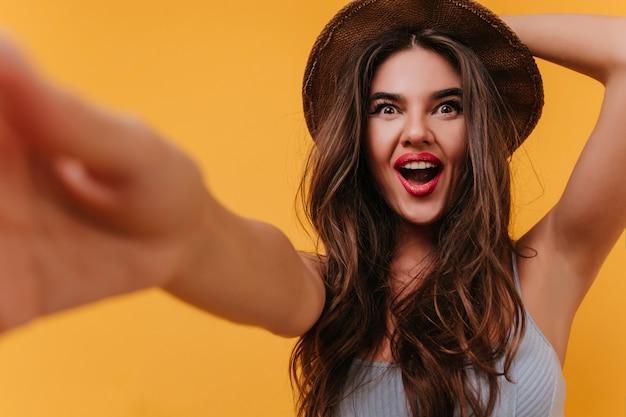 Ragazza europea soddisfatta con capelli castani lucidi che fanno selfie