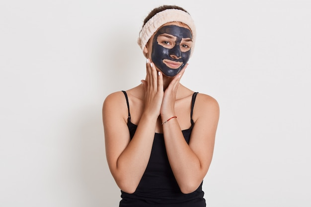 Pleased european woman applies nourishing clay mask on face, has glad expression, touches cheeks, having problem of dry skin.