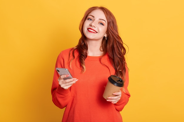 Pleased european woman dressed in casual orange sweater, poses, looks smiling at camera